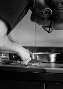 Chef Elia, proprietario di mainor che lavora in cucina